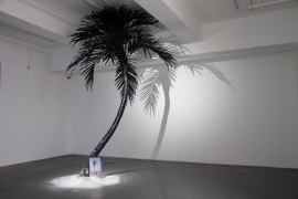 "Liang Ban, Pirate Utopias, 2018. Single channel video (0'47""), fake palm tree, white sand, monitor, acrylic, dimensions variable."