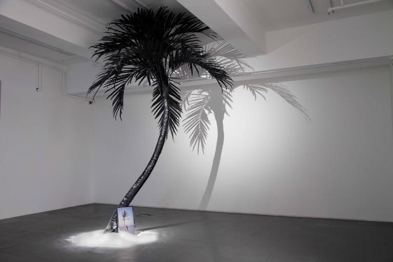 梁半,海盗乌托邦,2018. 单频录像(00'47''),人造椰树,白沙,显示屏,压克力,尺寸可变.