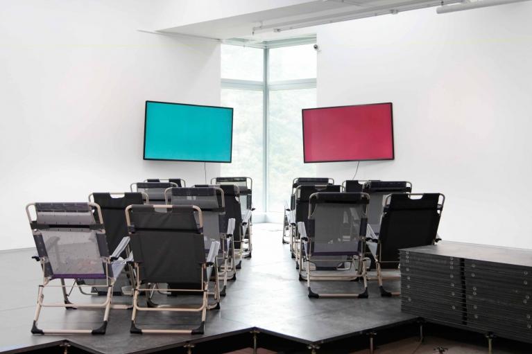 何恩懷,CX 888,2018。摺疊式躺椅,2個視頻,顯示屏,地氊,左邊視頻(綠色):28'01