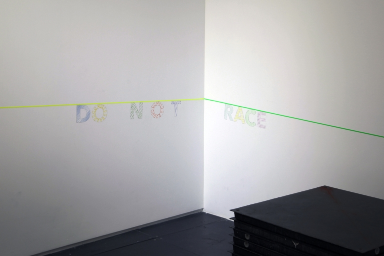 Christopher K. Ho, DO N O T RACE, 2018. Plexiglas letters, graphite and color pencil on wall, diagonal line, Dimensions variable.