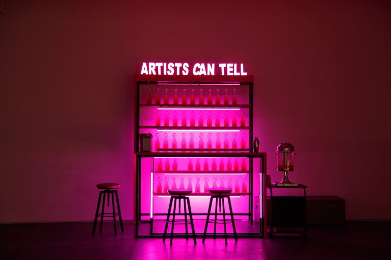 王欣,Artists Can Tell, 2016,桌、椅、招牌、LED灯、自制酒瓶、酷爱饮料、伏特加,240 x 210 x 210 厘米