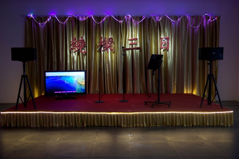 Mak Ying Tung, Sound of Music, 2017, Dual-channel video, audio set, red carpet, gold drapes, foam lettering, LED lights, disco ball, Dimensions variable.