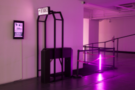 Wang Xin, No Starving Artists: Entrance, 2017. Turnstile, LED sign, 36inch LED TV, iron, stanchions, straps, headsets, audio recordings, LED lights, carpeting, tickets, computer, dimensions variable, entrance and turnstile (201 X 90 X 120 cm).